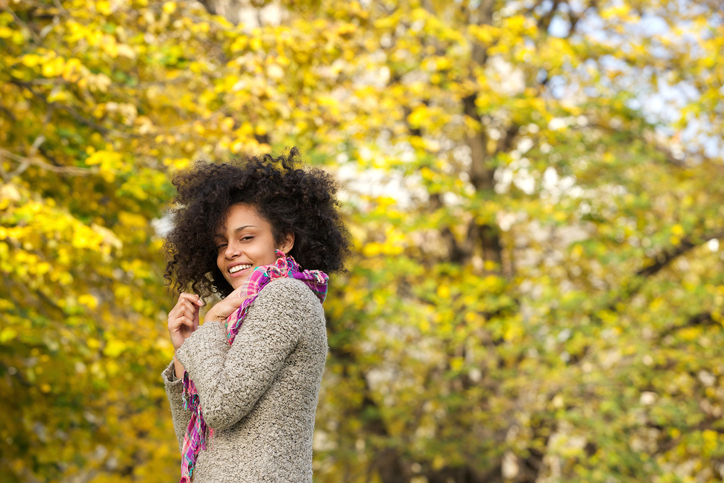 African American woman smiling outside in fall autumn natural hair