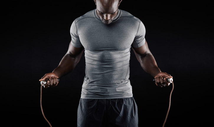 Muscular African american man jumping rope