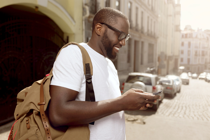 African American man smiling using cell phone