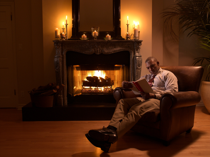 Senior African American man reading by fireplace