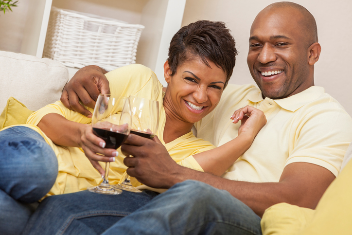 African American couple drinking wine on couch