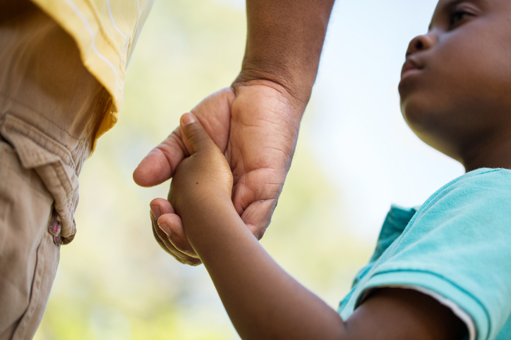 African American father and son holding hands