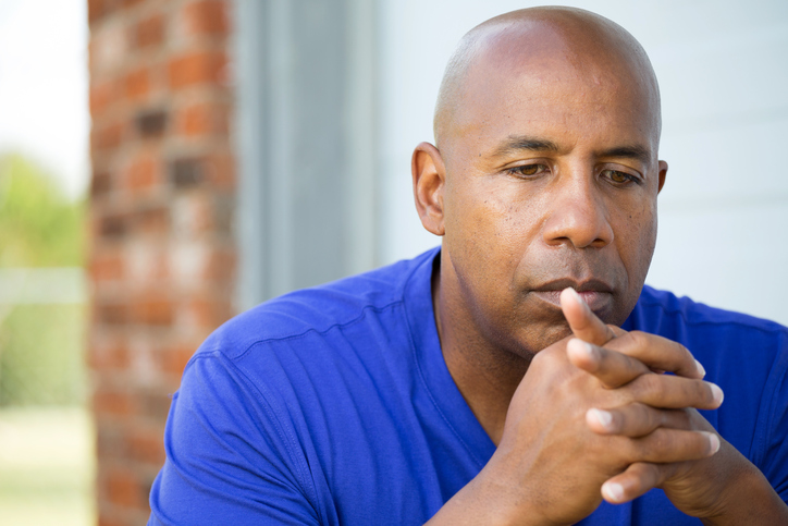 Older African American man looking thoughtful sad