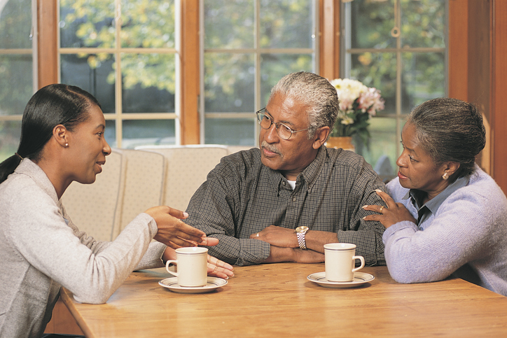 African American family talking at kitchen table