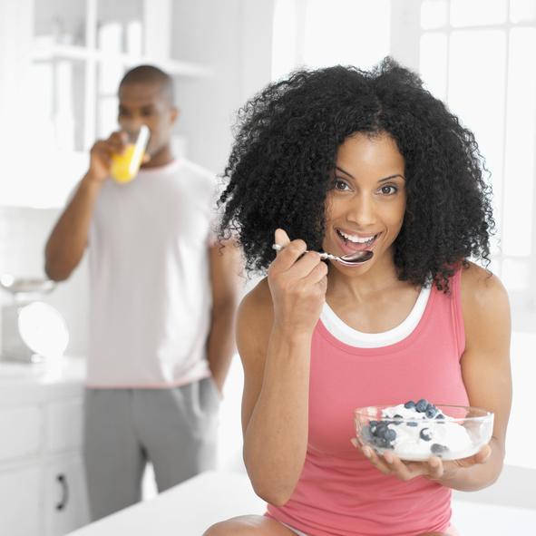 African American woman eating yogurt
