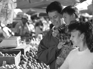 Photo of a family shopping for vegetables at an open air market.