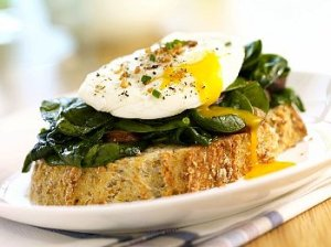 A breakfast meal of spinach, mushrooms and an egg on top of a piece of toast