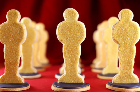 A series of Oscar-Award shaped cookies on a red surface