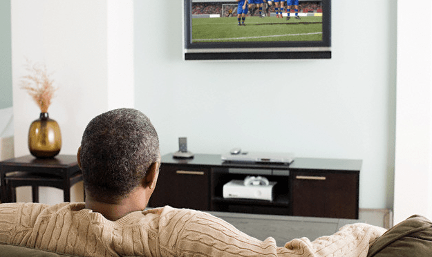 A rear view of a man watching TV