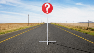 A question mark stop sign sitting on an open road