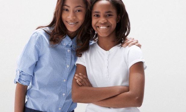 Two teen girls smiling, with one girl wrapping her arm around the other girl