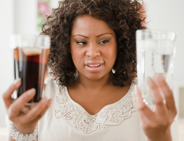 A woman holding glasses of both water and soda