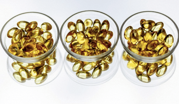 Three small glass bowls filled with omega-3 supplements