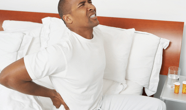 A man sitting in bed wincing and touching his back