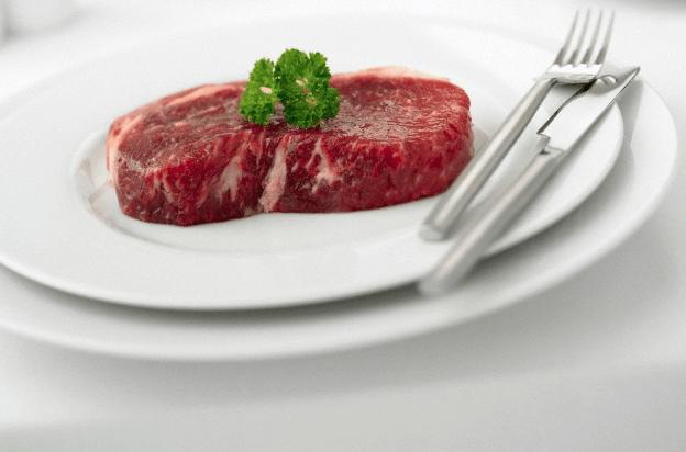A raw steak on a white plate