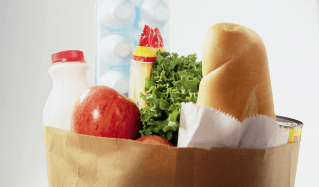 A close-up of a brown paper bag filled with groceries