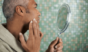 A man using a handheld mirror to examine his skin