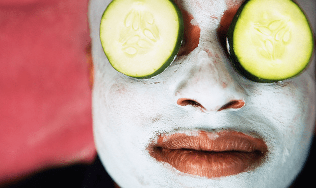 A man wearing a facial mask and cucumber slices over his eyes
