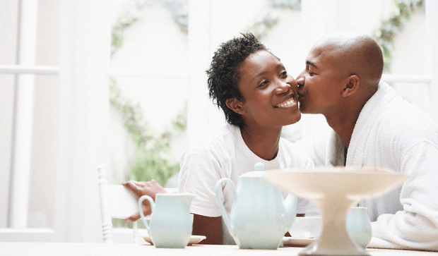 A man kissing his smiling wife as they sit at a table with mugs