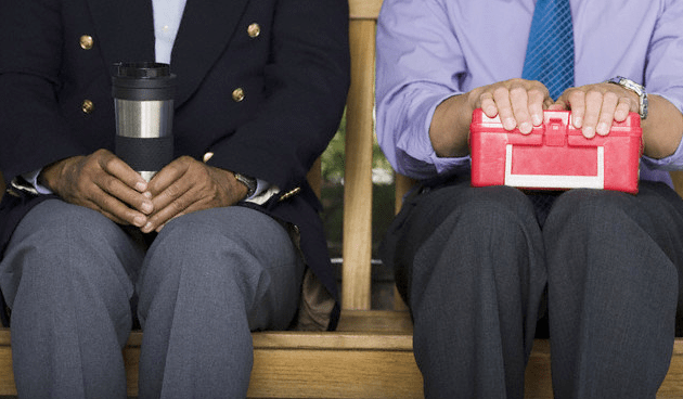 Two businessmen, one holding a coffee mug, and the other holding a lunchbox