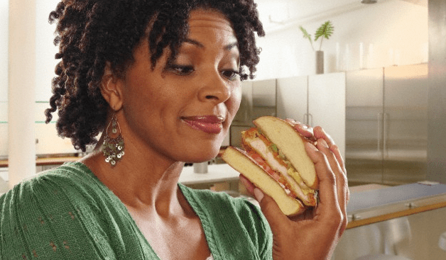 A woman holding and looking at a sandwich