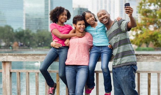 A father taking a picture of his family as they pose on a bridge