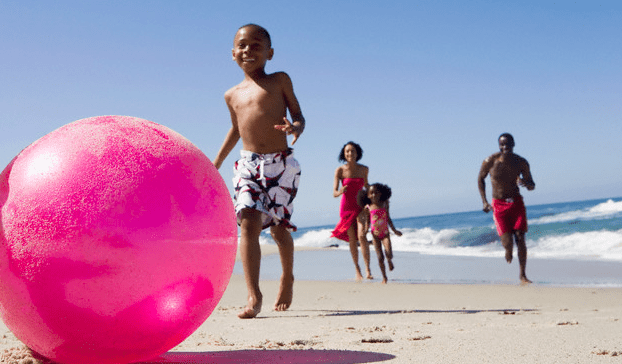 A family chasing after a pink beach ball on the beach