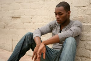 young african american man sitting with head
