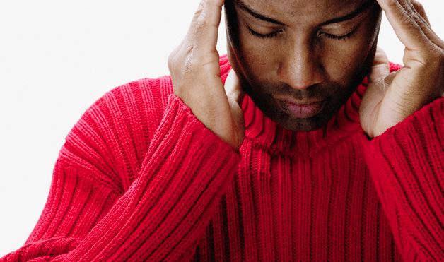 A man in a red sweater rubbing his temples with his fingers