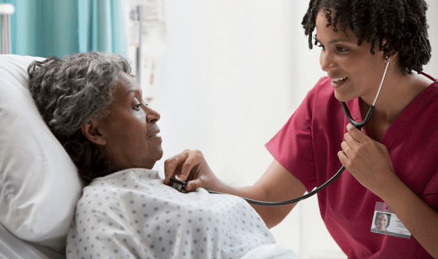 A doctor checking an elderly patient's heart with a stethoscope
