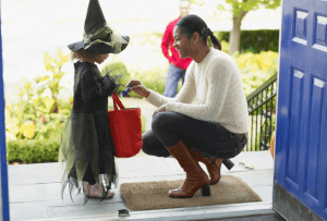 A woman kneeling down and giving candy to a little girl for Halloween