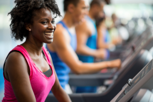 A smiling woman on the treadmill at the gym
