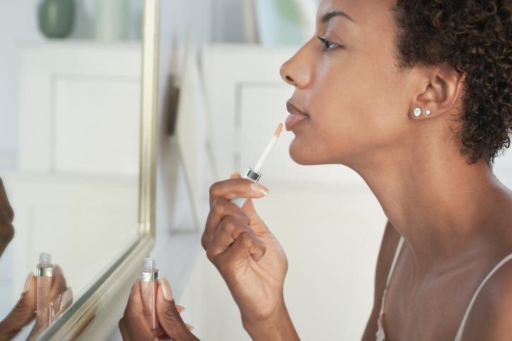african american woman mirror lipgloss make up