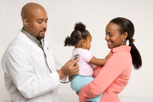 African-American male pediatrician examining baby girl being held by mother.