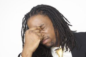 black businessman eyes closed pinching top of nose