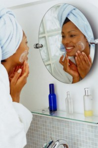 african american woman washing her face in the bathroom mirror