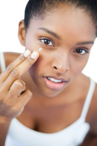pretty african american woman putting moisturizer on her skin