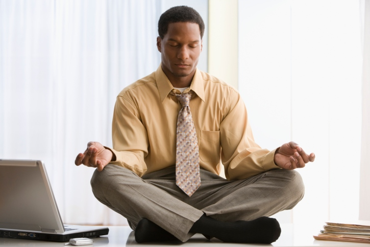 Black African American businessman meditating on desk