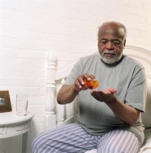 older african american man pouring pills from a prescription bottle into his hand