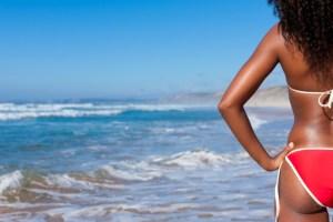 back view of african american woman wearing a bikini on the beach
