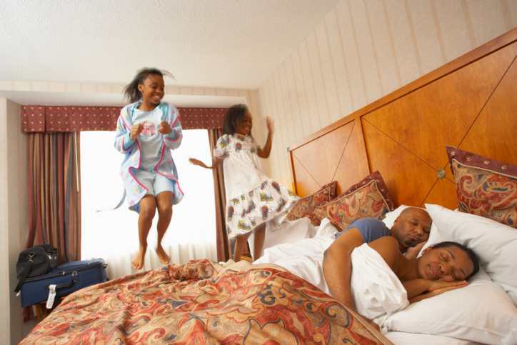 Girls jumping on hotel bed