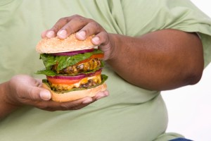 obese man holding double cheeseburger