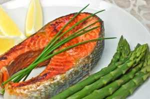 salmon steak dinner with asparagus and a lemon wedge