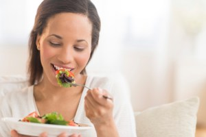 woman at home eating salad