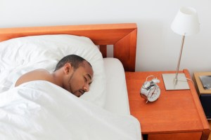 Young man sleeping next to Alarm Clock