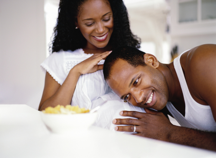 man resting his head on his wife's pregnant stomach