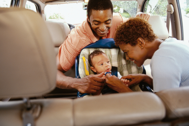 parents with baby in car