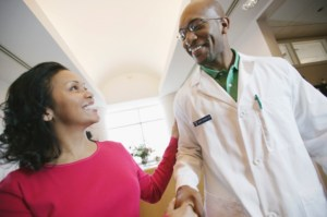 African American Black woman shaking doctors hand