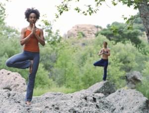 two women doing yoga poses on rocks