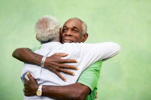 two older gentlemen hugging